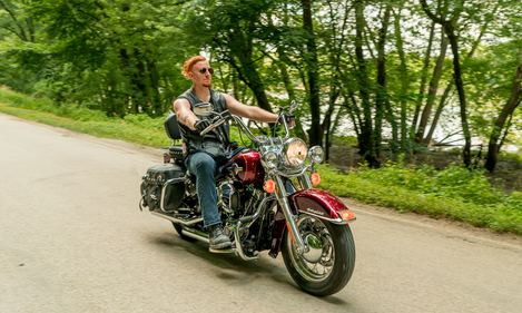 "Image of Jon ""Ginger"" Jansen, Biker Lawyer, on Meet the Crew page, riding Harley Motorcycle"